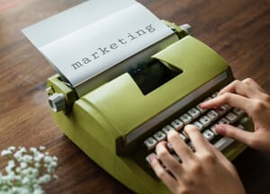 "A green typewriter with paper in it that says ""marketing."" Marketing is very important for video production."